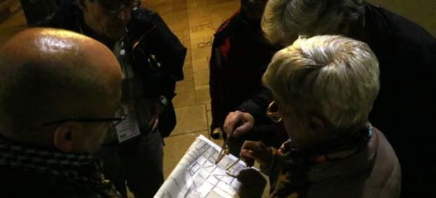 Un grupo de voluntarios observa un mapa con las calles de Sarrià en las que se ha hecho el recuento de personas sin hogar en Barcelona de este 2018.