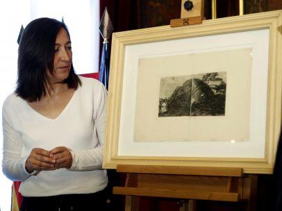 Juan José Borque, del Área de cultura de Zaragoza y Cristina Palacin, delegada de cultura, observan el grabado 'Paisaje con peñasco, construcciones y cascada', un inédito de Goya.