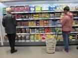 Consumidores llenando la cesta de la compra con alimentos.