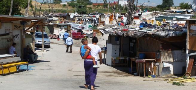 Una mujer con un niños en brazos en el poblado de chabolas de 'El Gallinero', en Madrid