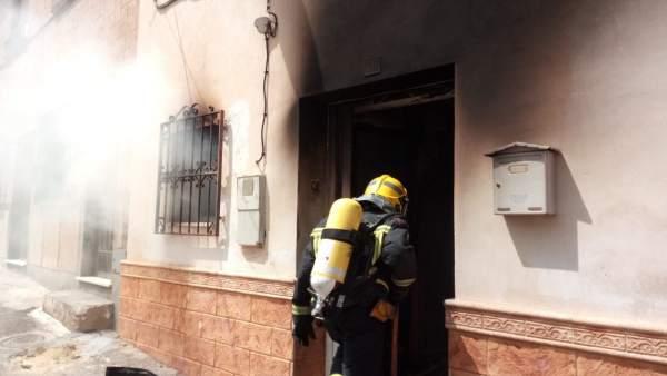 Un bombero entra en la vivienda siniestrada en Tíjola
