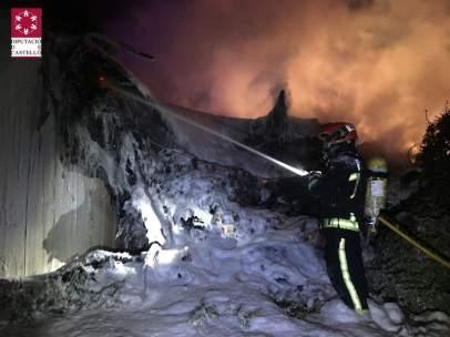 Un operario de los Bomberos sofoca el incendio del camión siniestrado.