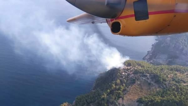 Los bomberos trabajan para extinguir el incendio en cala Estaellencs
