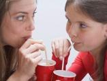 Madre e hija bebiendo con pajitas