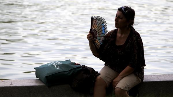 Una mujer se abanica por el calor