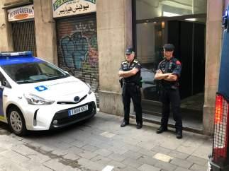 Dos agentes de la Guàrdia Urbana de Barcelona custodian un piso del Raval.