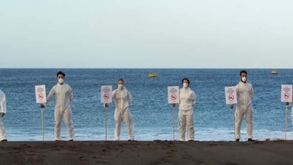 Activistas de Greenpeace cerrando simbólicamente una playa