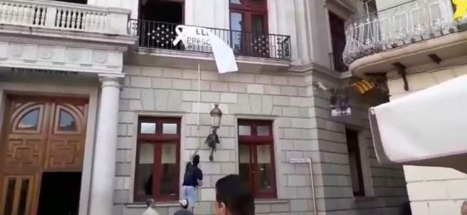 Ciudadanos retira una pancarta independentista en el Ayuntamiento de Reus.