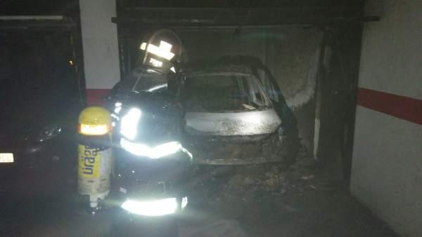 Los bomberos, trabajando para sofocar el incendio que calcinó el coche