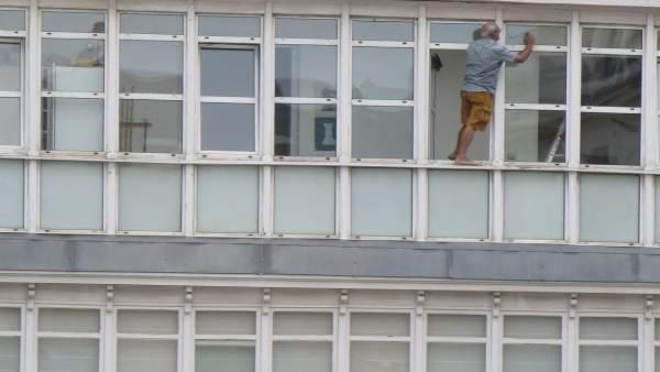 Hombre que limpia los cristales asomado a la ventana en Santander