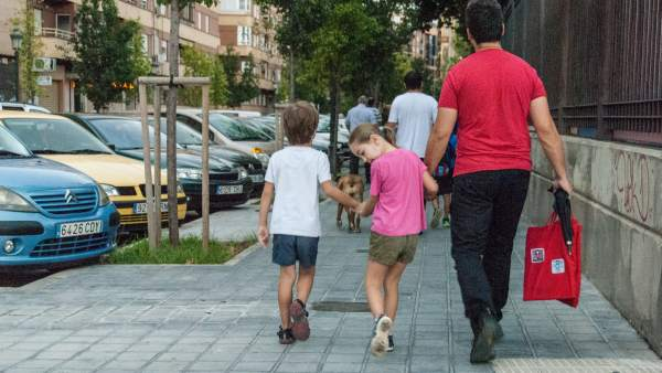Un padre con sus hijos rumbo al colegio.