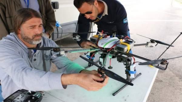 Ingenieros y pilotos de CATEC revisan un robot o dron antes de un vuelo