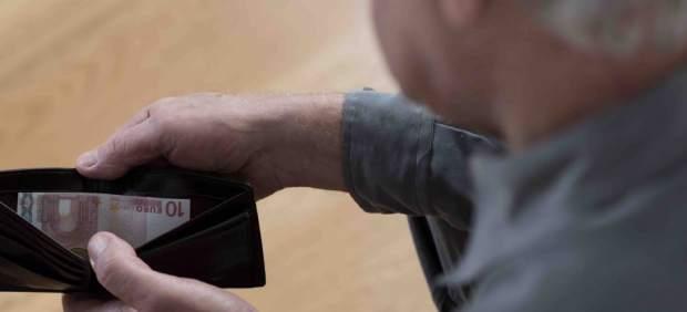 Un pensionista mira su cartera.