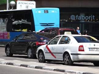 Imagen de un taxi, un vehículo VTC y un autobús público en Madrid.