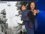 Una presentadora da el tiempo con su hijo a la espalda