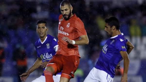 Benzema entre dos jugadores del Melilla.
