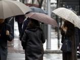 Peatones se cubren de la lluvia
