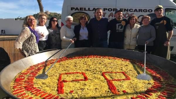Bonig en Oliva junto a la paella con el logo del PP