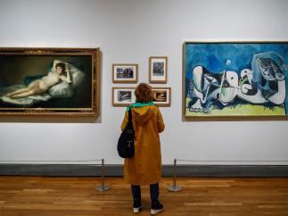 """Una persona observa las obras """" La maja desnuda"""" (1785-1800), de Francisco de Goya, y el """"Desnudo recostado"""" (1964), de Pablo Picasso, durante la presentación de la exposición """"Museo del Prado 1819-2019. Un lugar de memoria"""""""
