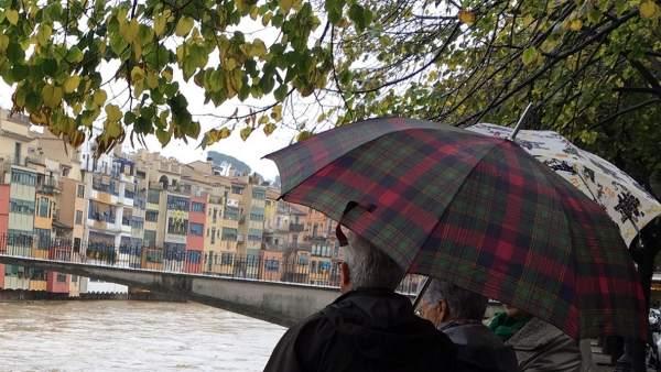 Visitantes mirando la crecida del río Onyar a su paso por la ciudad de Girona.