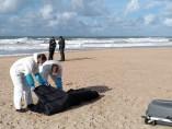Servicios funerarios recogen el cadáver de un inmigrante en la playa en Chiclana.