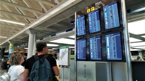 Dos viajeros consultan la información de vuelos en las pantallas del aeropuerto