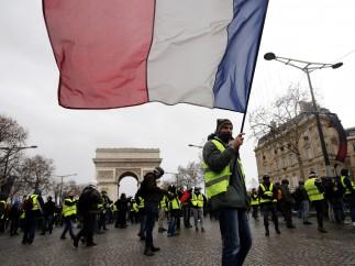 Un hombre con chaleco amarillo porta bandera francesa en una manifestación