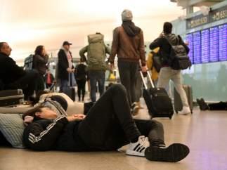 Una pasajera durmiendo en el suelo mientras otros viajeros transita por el vestíbulo de salidas de la terminal 1 del aeropuerto del Prat de Barcelona este 21-D.