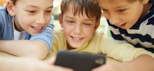 Tres niños con un móvil