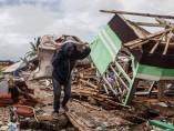 Hombre recoge pertenencia entre escombros del tsunami
