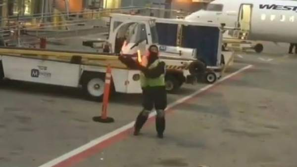 Un operario del aeropuerto bailando