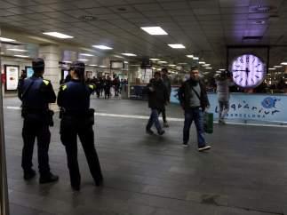 Dos agentes en la estación de Rodalies y Metro de plaza Catalunya, en Barcelona, donde se ha llevado a cabo un dispositivo policial contra el 'top manta'.
