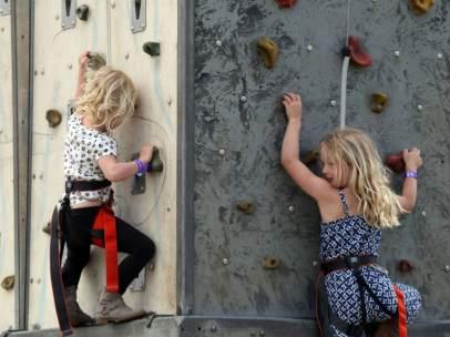 Dos niñas escalan en un rocódromo