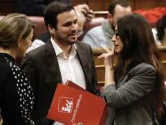 La nueva diputada de Unidos Podemos Sol Sánchez (d), sustituta de Íñigo Errejón que renunció ayer a su acta de diputado, acompañada por el líder de IU, Alberto Garzón (i), saluda a varios miembros de la formación a su llegada al pleno celebrado hoy en el Congreso