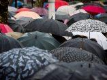 Varios peatones se protegen de las lluvias.