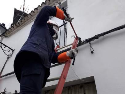 Un operador de suministro eléctrico corta una acometida ilegal.