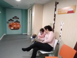 Un paciente pediátrico y su madre esperan en una sala de la Unidad de Fibrosis.