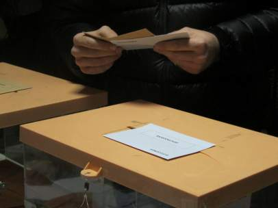 Persona con las papeletas en la mano, junto a las urnas.