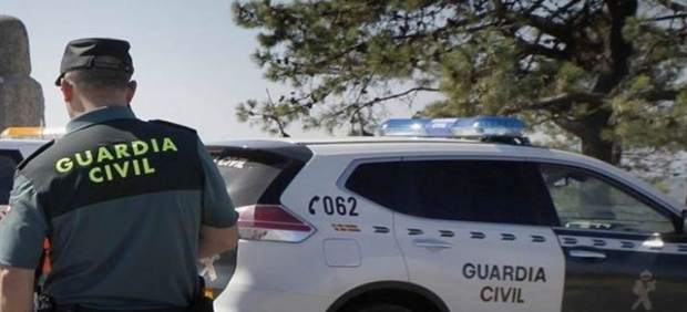 Imagen de archivo de un agente de la Guardia Civil junto a un coche patrulla