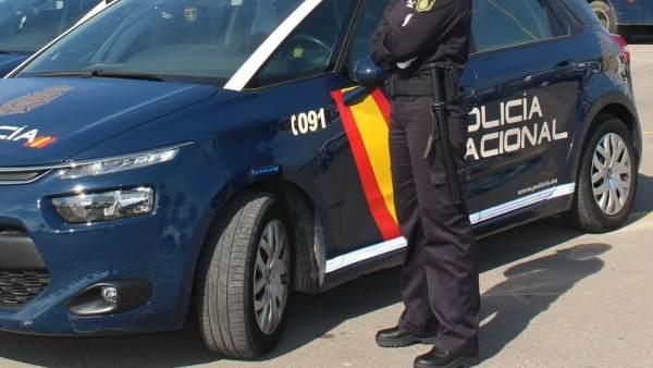 Agente y coche de la Policía Nacional