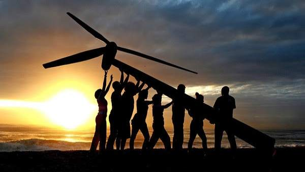 Greenpeace and Tcktcktck volunteers raise a wind turbine on the beach at dawn in