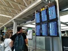 Dos viajeros consultan la información de vuelos