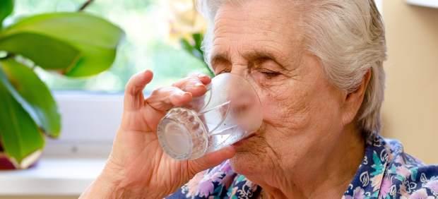 Anciana bebiendo agua del grifo