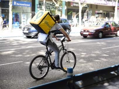 Trabajador de la empresa Glovo montando en bicicleta por Madrid.
