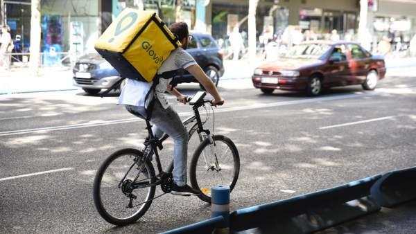 Trabajador de la empresa Glovo montando en bicicleta.