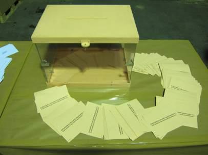 Un puñado de papeletas junto a una urna