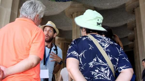 Dos turistas siguen las explicaciones de un guía turístico en el Park Güell.