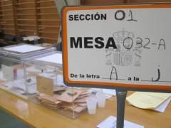 Cartel de una mesa electoral con las urnas al fondo