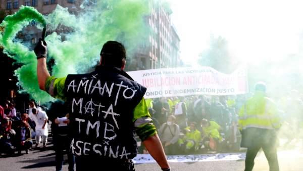 Un trabajador de TMB sostiene un bote de humo verde durante la manifestación de la plantilla del metro de Barcelona en protesta por la presencia de amianto en las instalaciones.