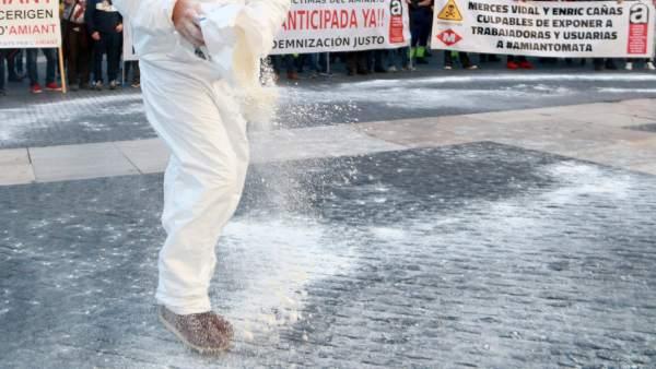 Manifestante en plaza Sant Jaume lanzando harina que simula ser amianto